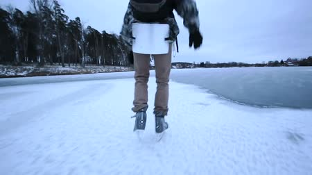 happy guy Ice Skating on a Frozen Lake, with a backpack, health lifestyle, montage Dostupné videozáznamy