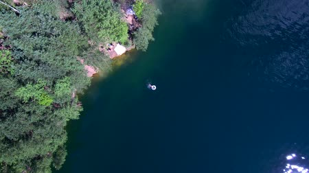 people swim in the lake, have a good time, shoot from a drone, aireal view