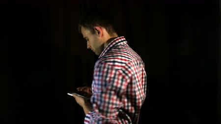 man in plaid shirt, hipster uses phone, surf internet on black background