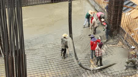 cement floor : workers pouring concrete mix on floor from concrete pumping truck. Stock Footage