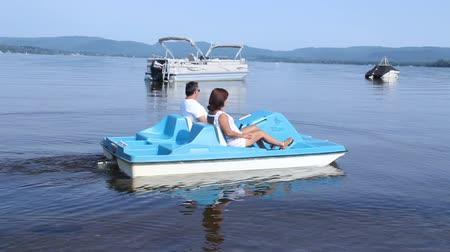 Mature couple on pedalo also called pedal boat on a lake at daytime