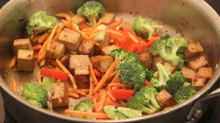 Tofu stir fry with vegetables cooking in pan