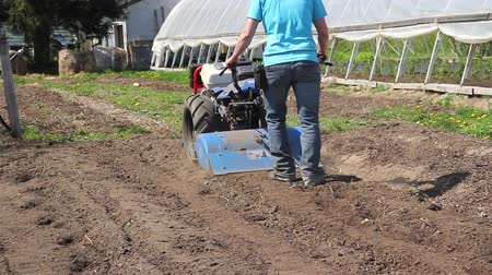 Woman worker driving rototiller tractor unit preparing soil on outdoor garden