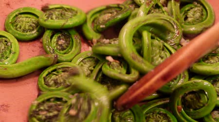 Ostrich Fern Fiddleheads wild veggie cooking in the pan with garlic