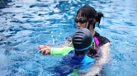 Mother is teaching her boy to swim in swimming pool