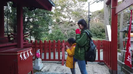 Tokyo, Japan: 21 March 2019: Mother and Daughter is praying in Kamakura shrine.
