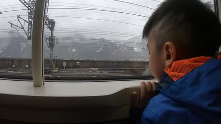 shinkansen : Little boy is looking out to Japan Yuzawa snow resort from Shinkansen train Stock Footage