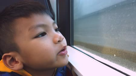 inside of train : Asian boy is looking out the train windows while traveling in slow motion Stock Footage
