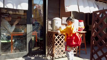 KAMAKURA, JAPAN - 2019 March 21: Little boy is pouring drinking water in to glasses in Japanese restaurant.
