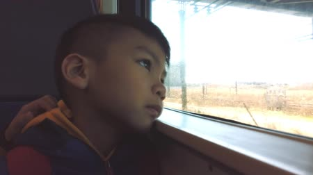Asian boy is looking out the train windows while traveling