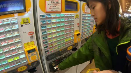 impressão digital : Hakone, Japan - 23 March 2019 : Tourist is buying food from Japanese automatic ticket vending machine.