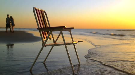 стулья : Chair on the coast in sunset with backgrounf of people silhouettes