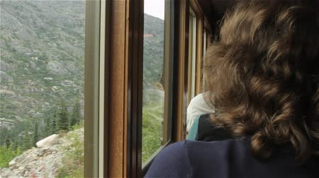 mozdony : A female rail passenger looking out train window to countyside.
