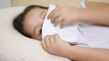 alergia : ill girl with paper tissue on the bed