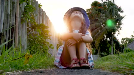 despreocupado : Happy little girl sitting on the grass and playing in summer garden. Outdoors. Sunset.