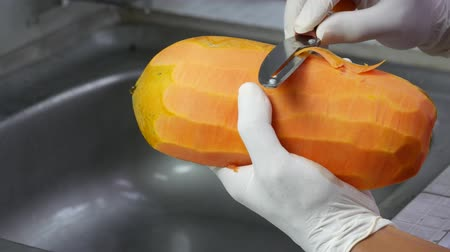 yarım uzunluk : Peel the ripe papaya with a sharp knife. Put on white rubber gloves for hygiene. one hand hold on papaya be careful at the sink