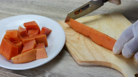 yarım uzunluk : Cut the ripe papaya into pieces. without peel. with the sharp knife on the cutting board. Put on white rubber gloves for hygiene .