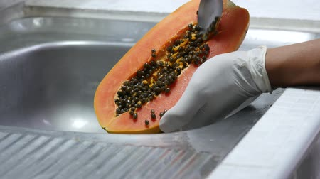 yarım uzunluk : wipe off papaya seeds after peel at the sink.  Put on white rubber gloves for hygiene . Stok Video
