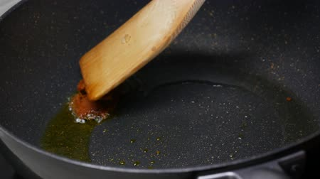 saute : stir fried the spices , curry paste  , food palm oil  together in the black pan and with wooden turner.