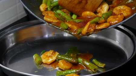 kari : pour stir fried yard long beans with shrimp , kaffir lime leaves, spices curry paste from the black pan to the stanless dish.