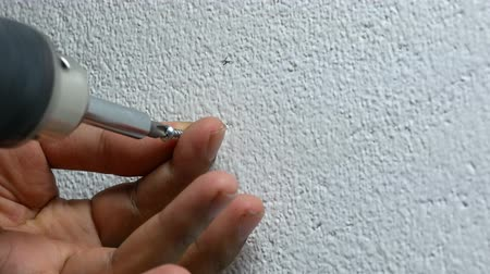 dowel : man hand using electric screwdriver to tighten the screw into plastic plug , wall anchors in the concrete cement white wall Stock Footage