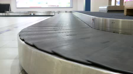 istek : empty conveyor belt moving in arrivals lounge of airport terminal for traveller , passenger or business man s suitcase