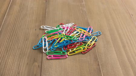 ordner : Colored paper clips on a wooden background time lapse.