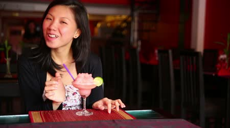 tüyler : Asian young woman drink cocktail alone at bar Stok Video