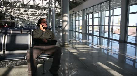 lounge : young man using mobile phone at airport