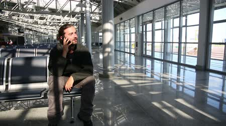 lounge : young man talking on phone at airport