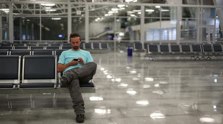 departure : young man using mobile phone at airport