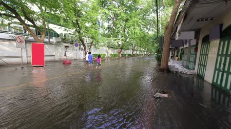floods : Street under flood in Bangkok Thailand. Life continues Stock Footage