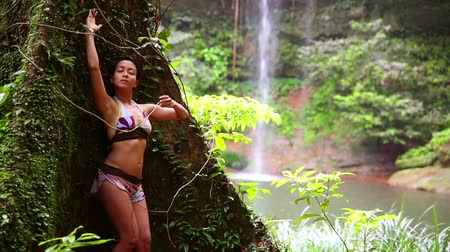kalimantan : Sexy girl leaning huge tree in rainforest background waterfall