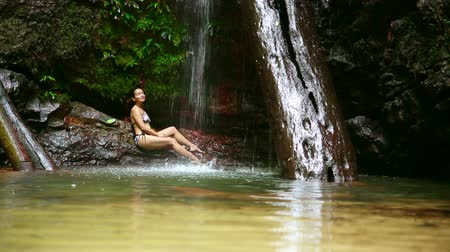 hidromassagem : sexy girl with bikini lying down in waterfall river
