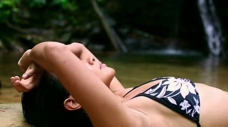 napping : sexy girl with bikini lying down in waterfall river