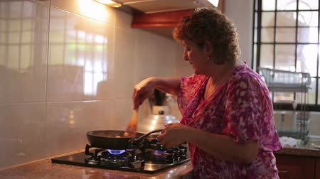 cooks : Mother preparing food at kitchen