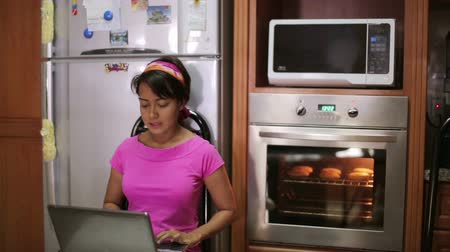 forno : woman sitting with laptop by oven in kitchen