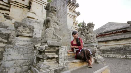 monkey temple : naughty monkey try to steal from balinese girl, uluwatu temple Stock Footage