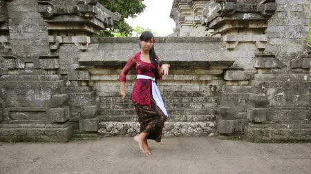 teatral : balinese girl dancing traditional dance in uluwatu temple, bali