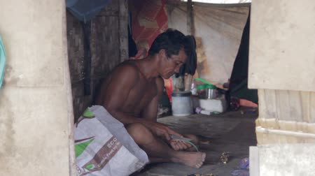 отходы : Adult man inside shack in a slum