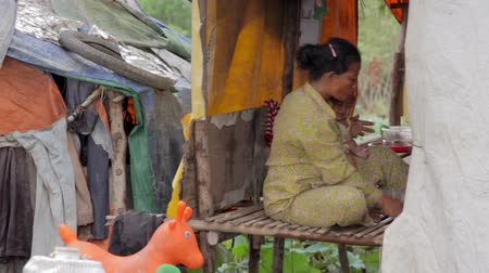 piersi : Mother feeding baby in cambodian slums, close to dump area