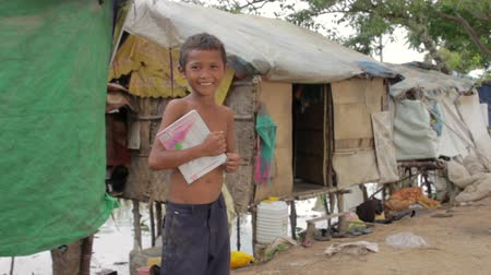 housing problems : Boy in slum holding book want to go school