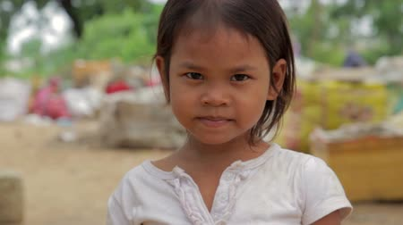 hladový : Cambodian girl in slums, garbages at background
