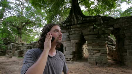 общаться : caucasian tourist talking with mobile phone, ruins in tropical jungle Стоковые видеозаписи