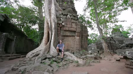 banyan : caucasian tourist travel in Ta Prohm temple, angkor, cambodia Stock Footage