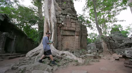 southeast : Visitor reading tourist information map in Ta Prohm temple, angkor Stock Footage