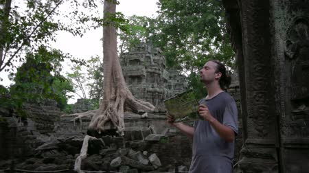 banyan : Visitor reading tourist information map in Ta Prohm temple, angkor Stock Footage