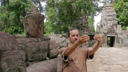 Ангкор : alone visitor takes own picture in preah khan temple, angkor