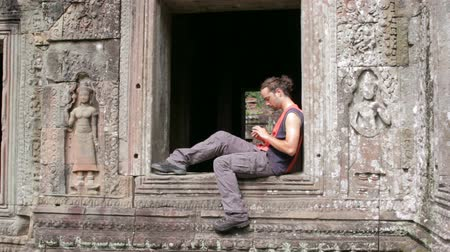 üzenetküldés : caucasian tourist using mobile phone in angkor  Stock mozgókép