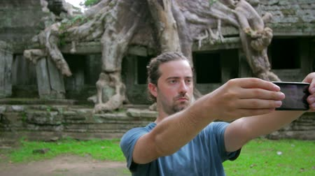 southeast : visitor taking picture bizarre nature of preah khan temple, angkor Stock Footage